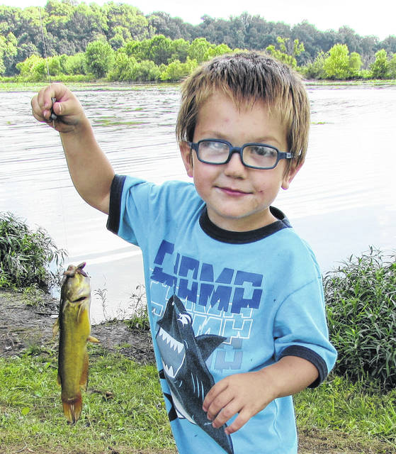 "Three-year-old Gabe Gibson enjoyed his last day of Cub Scout Day Camp at Rocky Fork State Park by hauling in this foot-long catfish Friday afternoon. When asked what kind of special bait he used to lure the fish in, he told The Times-Gazette, ""Whatever Papaw puts on the hook."" Gabe is the grandson of Marti and Ty Mick of South Salem."
