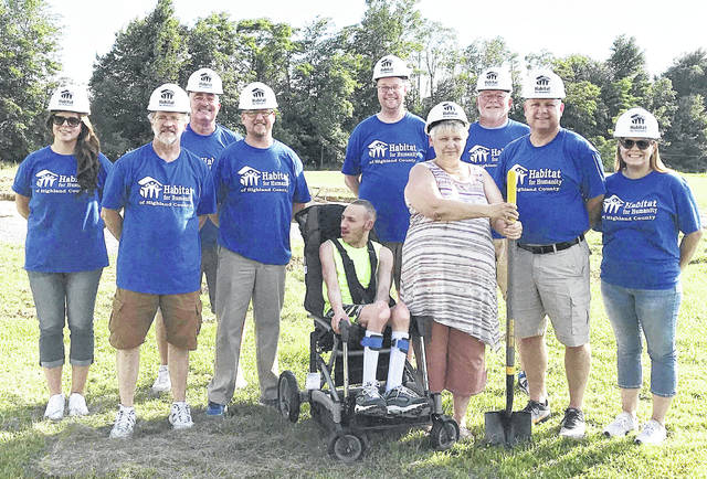 Habitat for Humanity board members, from left, Kelli Rosselott (executive director), Daryl Mount, Steve Conrad, Marc Bayless, Denny Kirk, Dave Minton, Richard Warner (board chairman) and Ashley Campbell are pictured at a recent groundbreaking ceremony. Pictured in front are the future new home owners, Kathy and her son Myles.