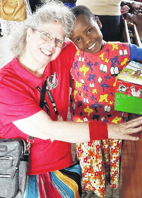 Local Operation Christmas Child coordinator Barbara Lanctot is pictured with a shoebox recipient in Tanzania.
