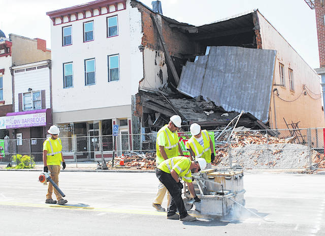 With a collapsed building in the background, Ohio Department of Transportation workers paint new lines Thursday in the 100 block of West Main Street in Hillsboro.