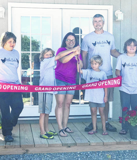 Mother Cluckers Farmhouse owner Heather Hughes is pictured at the store's grand opening with members of her family.