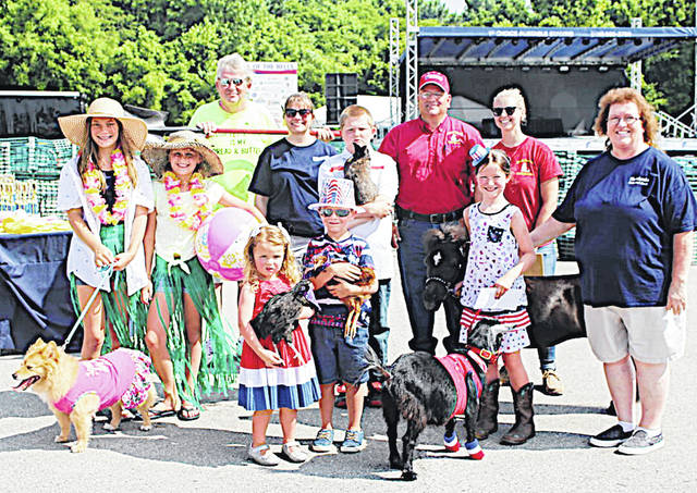 Pictured are Paul Pence, chairman of Merchants National Bank and official pooper scooper; judges, Amy Baldwin of Merchants National Bank, Steve Ventura and Sarah Rumpke of Master Feed Mill, and Bertha Hamilton, MNB chairman's secretary/HR; Meredith Dietrick and Kayla Seeling with their dog named Piper the Beach Babe; Nicholai Wing with his bunny named Mother; and Sweepstakes Winner Ava Lohrey with mini horse named Diamond and goat named Peter; Evan Lohrey with his chicken named Spiderman; and Ellie Lohrey with her chicken named Sweetie.