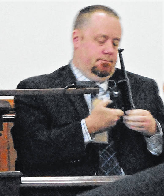 Andrew McClelland of the Bureau of Criminal Investigation & Identification shows the jury the alleged murder weapon during James Carver's murder trial Wednesday in Highland County Common Pleas Court.