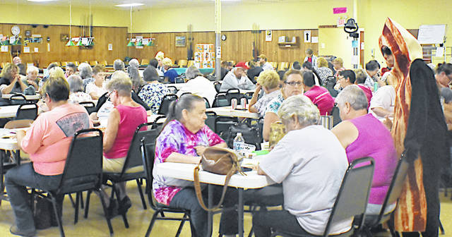 Mr. Bacon (far right), otherwise known as Aidan Kirk, validates a player's Bingo card as he volunteers at the Highland County Senior Citizen Center Bacon Bingo event on Saturday.