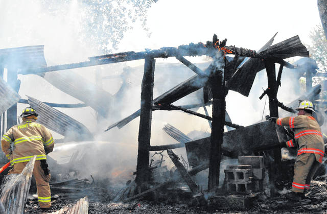 Firefighters battle a blaze that destroyed a corn crib on David Wolfenbarger property Friday afternoon at 9755 S. Careytown Rd., north of Hillsboro.