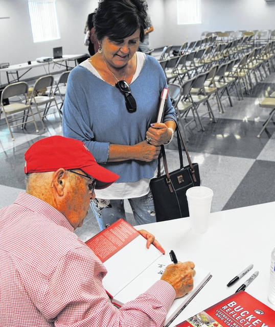 "Ohio State football broadcaster Jack Park was in Leesburg Saturday for the annual Leesburg Festival. He is shown here autographing a copy of his book ""Buckeye Reflections"" for Leesburg resident Diana Fordyce. Proceeds from sales of Park's book benefitted the fundraising efforts of the Leesburg Area Historical Society in restoring the village's train depot."