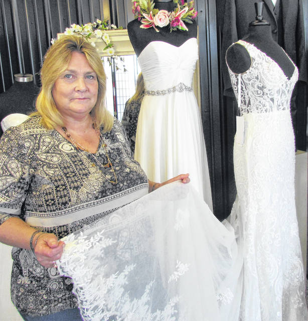 Main St. Tux Bridal & More's manager Diana Waldman holding the train of one of the many beautiful gowns at her store at 140 W. Main St. in Hillsboro.