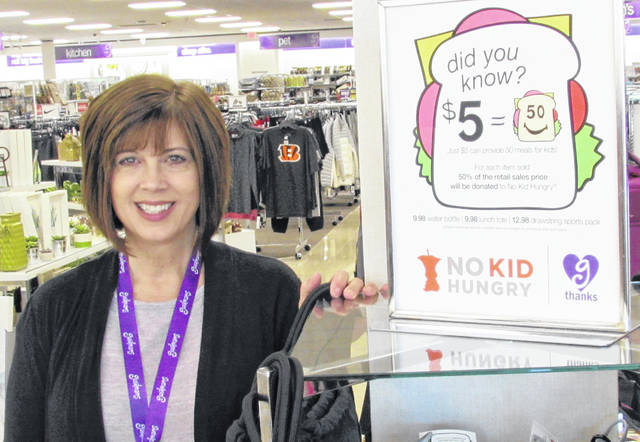 Pam Wilson, manager of the Hillsboro Gordmans store, stands next to the display that encourages shoppers to help with the No Kid Hungry campaign.