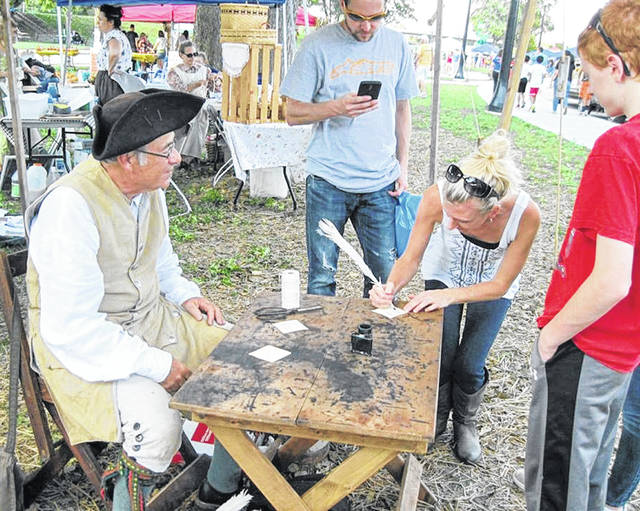 Scenes like this one of a Grassy Run Historical Arts Committee member displaying quill writing will be part of Pioneer Day on Saturday at the Scott House in Hillsboro.