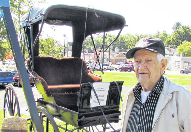 Howard Ellis, who owned the Hillsboro Dairy Queen for 45 years, is shown enjoying the history on display in front of a Belfast community exhibit at Saturday's Pioneer Day on the grounds of the Scott House in Hillsboro. The 94-year-old Hillsboro resident said he remembers his mother driving a similar buggy when he was a child. The vintage 1885 doctor's buggy, owned by Galen Neal, was originally made in Galion. Neal and he said he bought from a farmer in Scioto County and later had it restored.