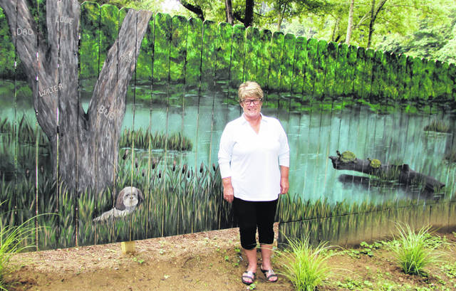 Local artist Jeanine Mullenix stands in front of her creation, a 56-foot long mural of a relaxing lake scene that was once just a privacy fence.