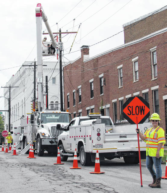 Katelyn Yates of Road Safe Traffic Systems, right, kept traffic flowing and safely away from an AEP crew working to restore power and internet service near the intersection of Beech and North Highstreets in Hillsboro following Thursday's storms.