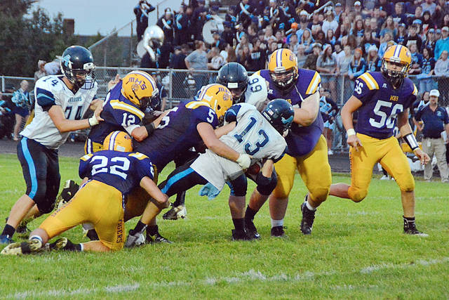 McClain Tigers, from left, Dalton Mischal, Blake Gall, Sam Faulconer, Ryan Tite and Justin Kegley stop an Adena ball carrier in Friday's game at McClain Field.