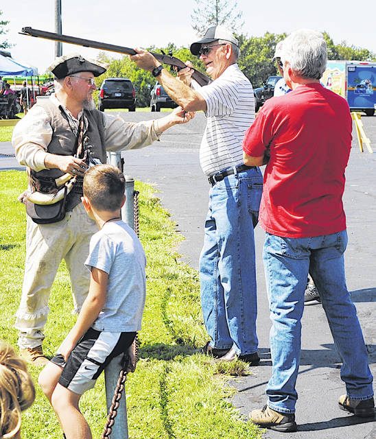 Hillsboro Safety and Service Director Dick Donley gets a lesson on shooting a flint lock rifle during Pioneer Day hosted Saturday by the Highland County Historical Society.