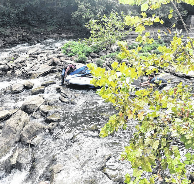 Two individuals attempt to move a Jet Ski after it went over the dam Saturday at Rocky Fork Lake.