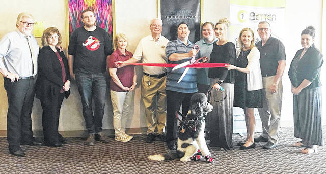 John Sutton and Teresa Woodrum (center holding scissors) are pictured with Star Cinema and Highland County Chamber of Commerce representatives during a recent ribbon-cutting ceremony.
