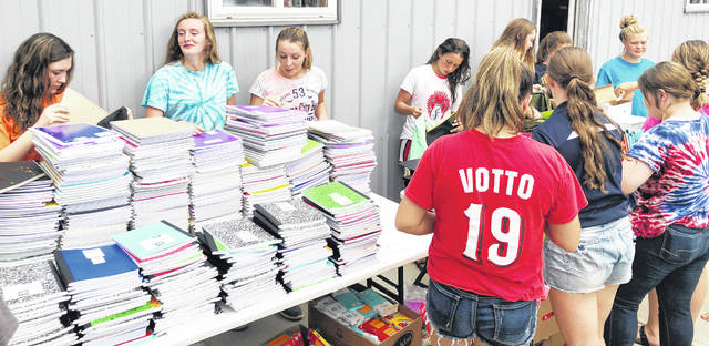 Hillsboro FFA members pack notebooks into backpacks that were distributed to Hillsboro fourth grade students.