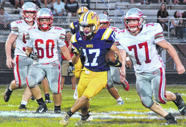 #17 Matt Bliss runs the ball for McClain, pursued by #60 Garrett Elzey and #77 Jeffery Zimmerman of East Clinton.