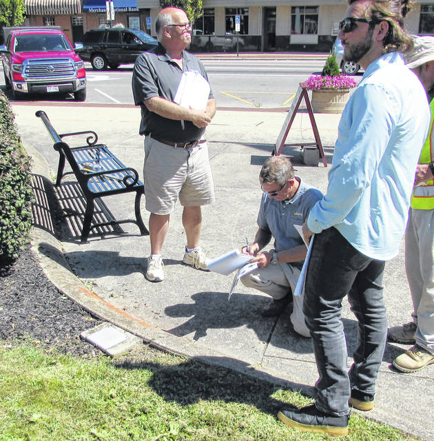 Engineers from Evans Landscaping, headed by Jim Bailey (kneeling), and City of Hillsboro officials are shown taking preliminary measurements and doing infrastructure location for the proposed courthouse square fountain. A spokesman for the Bagshaw family, which is underwriting the project, previously told The Times-Gazette that the new fountain is a gift to the City of Hillsboro and Highland County, and that the family is footing the bill, which is now in excess of $100,000. Bailey said construction on the fountain could begin in the next few weeks.
