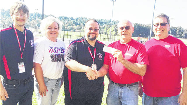 Glenn Roush and Tom Barton (right) present a check from the Hillsboro High School class of 1969 to the Hillsboro High School band. Also pictured, from left, are assistant band director Jonathan Jacky, Donica Grow and HHS Band Director Kevin Grow. Not pictured is assistant band director Joe Jacky.
