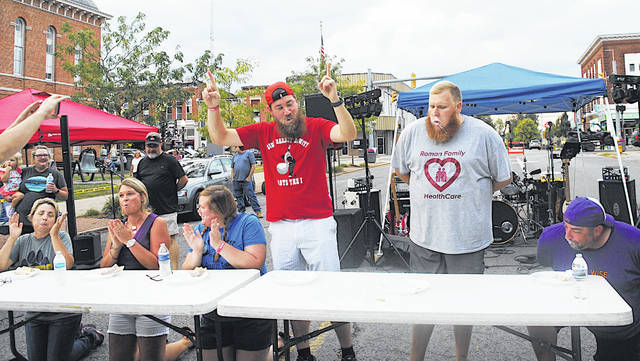 David Weaks, assistant band director and a math teacher at Greenfield Middle School, celebrates after winning the first annual Celebrity Cream Puff Eating Contest at G3's 2019 Oktoberfest.
