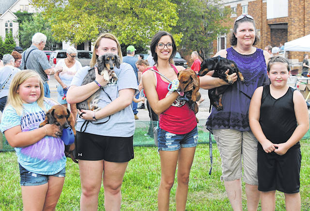 The winners of the Doxie Derby pause for a photo after the championship round. The winner, Pablo, and his owner, Jennifer Stroud, are on the far right. Pablo has won the Doxie Derby two years in a row.