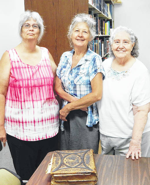Mary Hawthorne, SOGS research librarian, center, accepts the Hill family Bible from Barbara Woodbridge Copas, left, and Teresa Woodbridge Blanton.