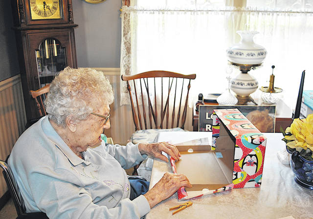 Ruth Meranda, 97, sits at her kitchen table wrapping an Operation Christmas Child Shoebox.