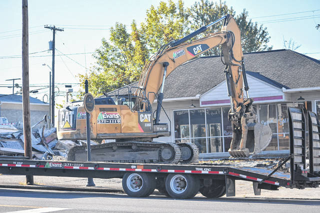 An Evans Construction crew is pictured Friday taking down a canopy at the former BP station in the 100 block of West Main Street in Hillsboro.