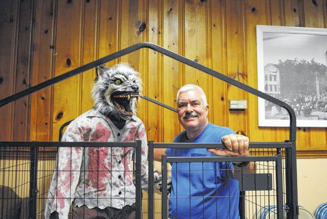 Retired deputy Steven Conrad stands next to his favorite Halloween animatronic: a wolfman.