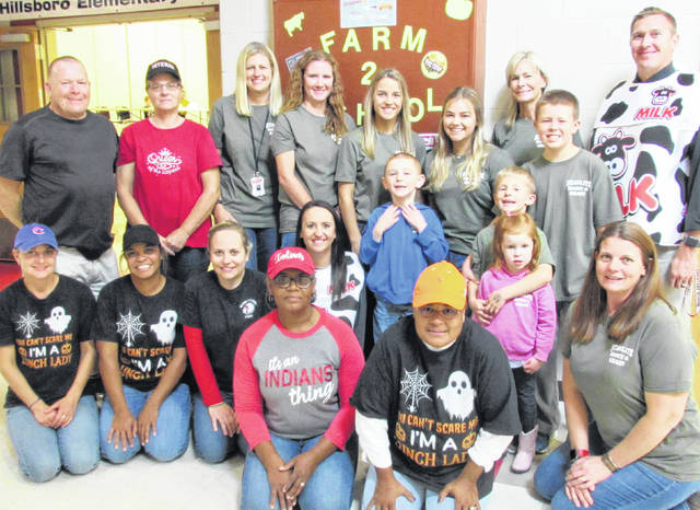 Hillsboro City Schools employees and representatives of Starlite Dairy and Grain helped students at Hillsboro Elementary School enjoy free ice cream Friday as part of the Farm to School program. Superintendent Tim Davis, shown at right, traded in his administrator's garb to don a dairy cow costume vest to help workers hand out the four-flavor treats to students.