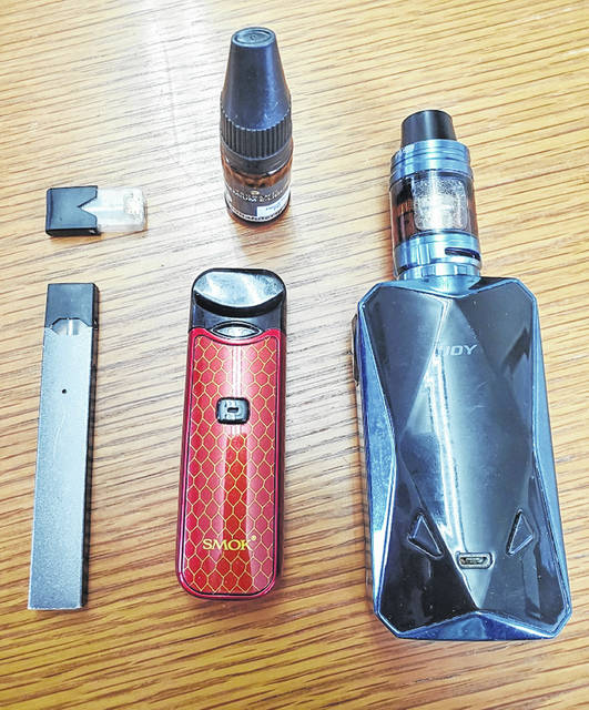 Pictured in the top left corner is a vaping pod that plugs into an electronic smoking device. To it's right is a filler bottle, used to refill an empty pod. The rest of the items pictured are various vaping devices.