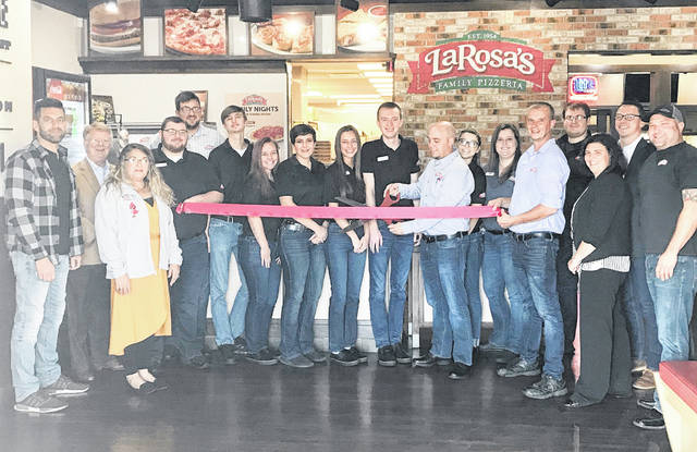 Last Thursday the Highland County Chamber of Commerce joined LaRosa's in celebrating the one year anniversary of opening its Hillsboro location. After acquiring the building at 589 Harry Sauner Road owner Tim O'Hara remodeled and opened for business Oct. 22, 2018. LaRosa's recently changed the wings they use, an inspiration originating from the Hillsboro location. The dining room has both tables and booths to comfortably accommodate the whole family. You can also watch your favorite team on the TVs throughout the dining room. The delivery area will soon be expanding to New Vienna. Many people question calling a 513 area code to order a pizza in Hillsboro which O'Hara explained. All orders are taken by guest service representatives at one centralized location. They focus on nothing but orders and customer service. The orders are sent directly to whichever location is chosen for the pick up or delivery within seconds of order submission to be made locally. Stop by on Oct. 31 and see General Manager Shawn Shelton (holding the scissors) and the team that will be passing out candy for trick or treat night.