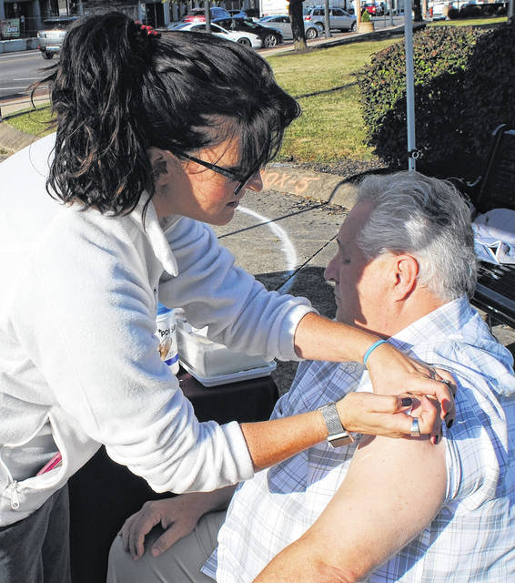 As part of its ongoing efforts to encourage people to protect themselves against the flu, the Highland County Health Department had another of its remote clinics Wednesday morning on the Highland County Courthouse square in Hillsboro. Director of Nursing Bonnie Rusch is shown administering the vaccine to the Rev. Tom Zile, pastor of the Hillsboro Church of the Nazarene.
