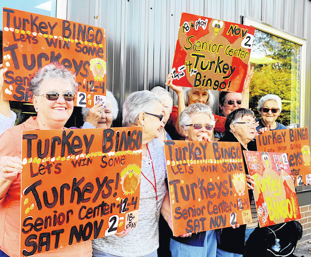 Highland County Senior Citizens members pose with signs advertising the center's Turkey Bingo event on Saturday, Nov. 2. One center will give away 100 turkeys at the event.