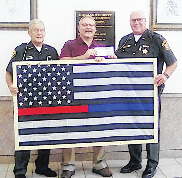 Hillsboro First United Methodist Church Pastor Derek Russell (center) presents a check for $1,000 to Highland County Sheriff Donnie (right) and former sheriff Tom Horst.