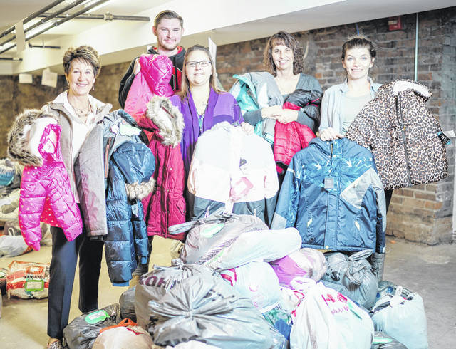 Adena caregivers are pictured with some of the 1,200 coats they distributed this year through the Coats for Kids program.