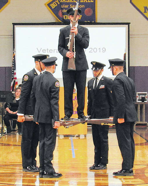 The McClain Cadet Corps Drill Team is shown at the end of its Veterans Day performance. When the cadet standing on the guns was lifted, an audible gasp rose from the crowd.