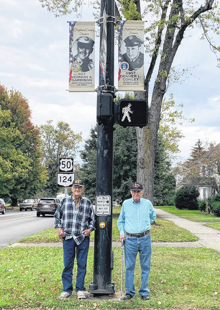 Korean War veterans Vernon Garrison, left, and Denver Conley stand beneath their banners on East Main Street in Hillsboro.