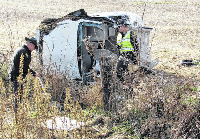 Shown from left, Ohio State Highway Patroll Troopers James Brooks and David Beck conduct their investigation of a one-vehicle rollover accident Friday on SR 753 south of Greenfield.