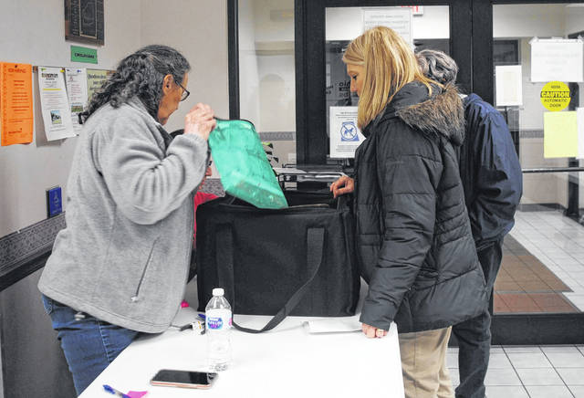 On Tuesday night, election volunteers Ginger Cox and Katrina Tolliver unpack the ballots brought to the Highland County Board of Elections by poll workers Bev Carroll and Myra Phillips. Pictured, from left are Cox, Tolliver (partially hidden), Carroll and Phillips (partially hidden).