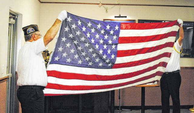 Two members of the Hillsboro VFW Color Guard hold the American flag just before a folding of the flag ceremony.
