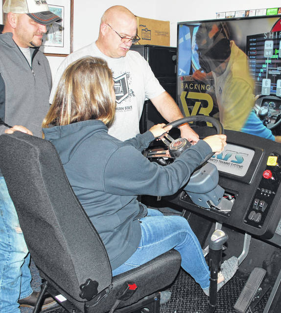 JT Smith, far right, Southern State Truck Driving Academy director/training manager, works with a student on a virtual reality simulator that allows for shifting and driving training without getting behind the wheel.