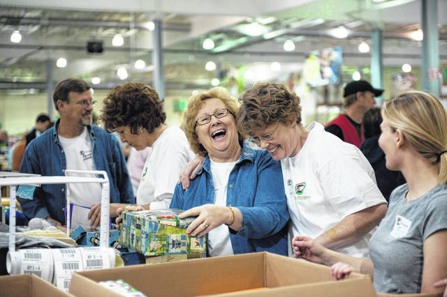 Volunteers at an Operation Christmas Child processing facility pause while packaging wrapped shoeboxes to be shipped around the world.