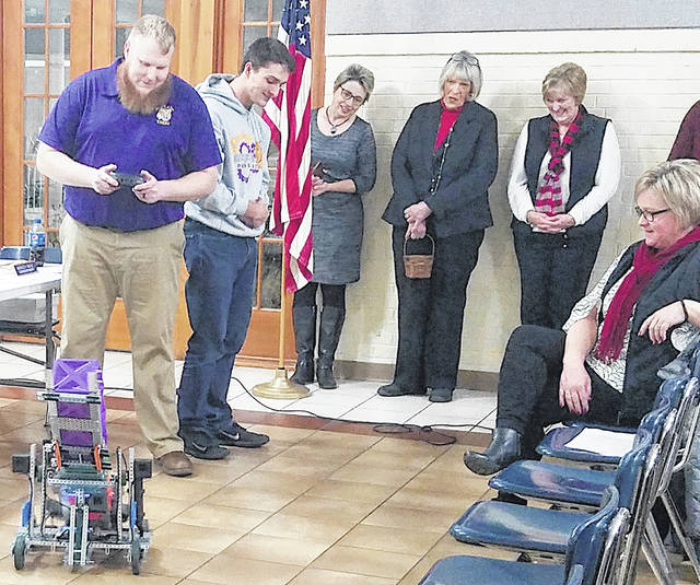 School board member Charley Roman drives a robot built by one of the McClain High School robotics teams. Next to him is robotics team member Blake Gall. In the background (l-r) are superintendent Quincey Gray and school board members Marilyn Mitchell and Sandy Free.