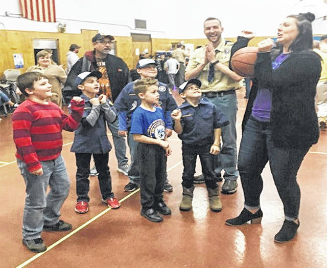 Molly Barnett from Highland County Board of DD's Community First department demonstrates how to shoot or pass a basketball using only the elbows at a Nov. 21 Highland County Boy Scout meeting.
