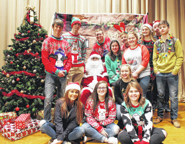 On Dec. 11 the McClain FFA Chapter hosted Children's Christmas for all of the elementary students. The auditorium in the McClain High School was turned into Santa's Workshop and all of the students were able to come over and visit Santa. The chapter asked for a $2 donation for the kids to take a picture with Santa and all funds went toward buying presents for the 13 kids the chapter adopted for Christmas. After taking a picture with Santa, the kids told the elves what they wanted for Christmas and received a cookie. Mrs. Lovett's class baked all of the cookies to give to the kids. Some of the FFA students are pictured with Santa Claus.