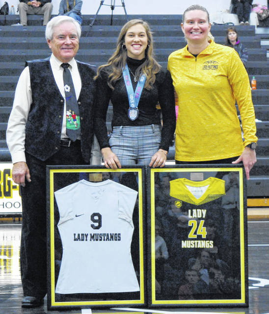 Coach Dennis West and Coach Whitney Lewis honoring Peyton Scott with her high school soccer and basketball uniforms.