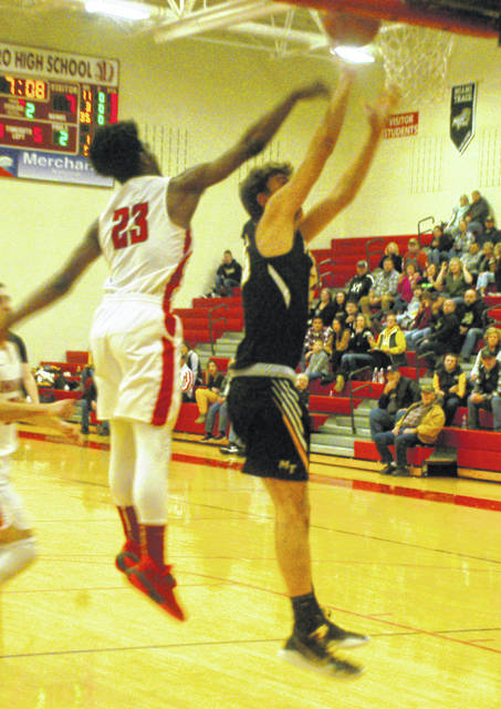 Indians' Jakwon Clark going up for a block as Hayden Hunter of Miami Trace tries to score.