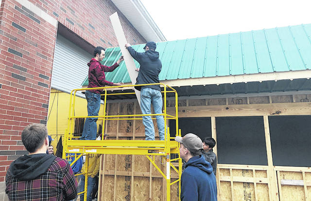Gavin Puckett, left, and Casey Jordan work together on the roofing for the new Hillsboro FFA food booth.